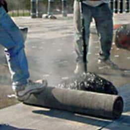 dos contratistas aplicando un sistema de techo por asfalto caliente
